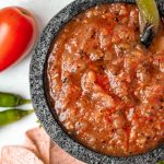 Salsa roja in stone molcajete with pepper garnish and tomato and pepper props