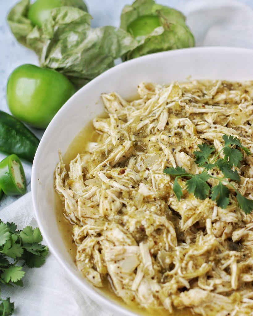 White bowl with chicken chile verde. Tomatillo garnish